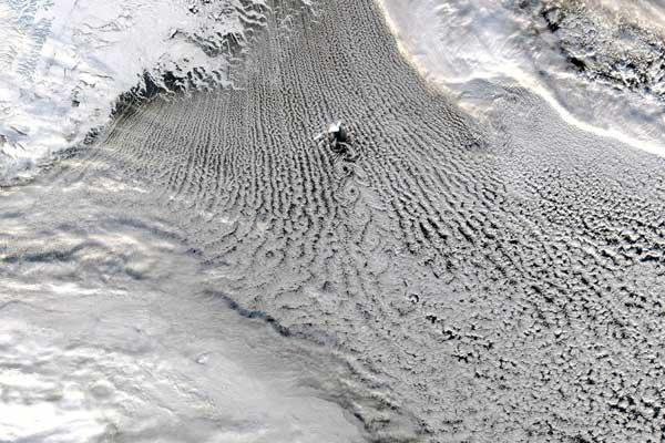 """The """"cloud streets"""" over the Greenland and Iceland seas shown in this satellite image exist as a result of heat and moisture transfer processes that warm the atmosphere and cool the ocean"""