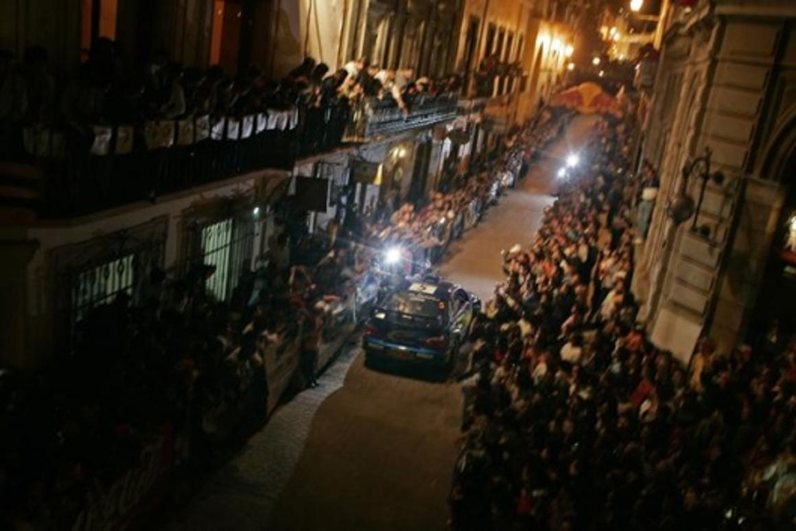 Subaru's Petter Solberg parades through town on the night preceding the rally start