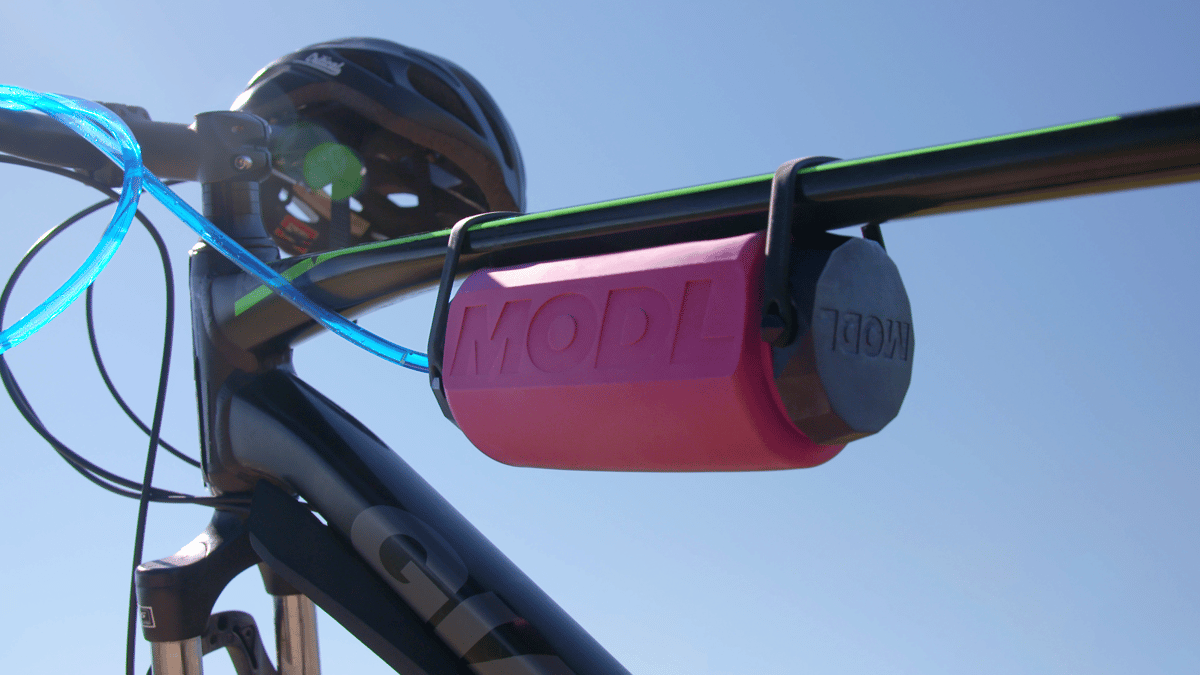 The MODL with its Flow Mod installed, mounted on a bike frame using its integrated silicone straps