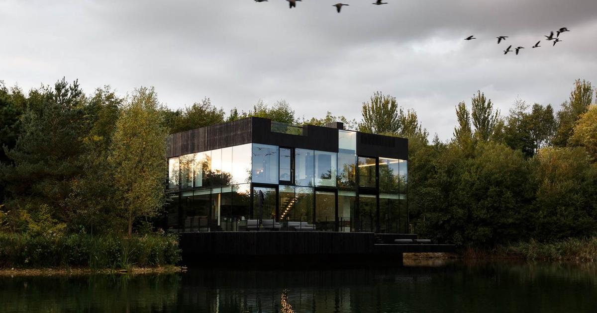 Shimmering sustainable home on the lake uses glass to give residents a floating sensation
