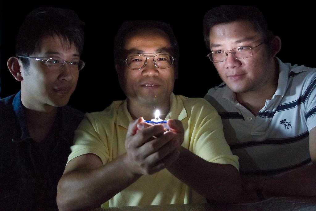 UGA physics professor Zhengwei Pan, flanked by Feng Liu (left) and Xufan Li, holds a prototype of a new LED that produces a warm white light from a single emission source
