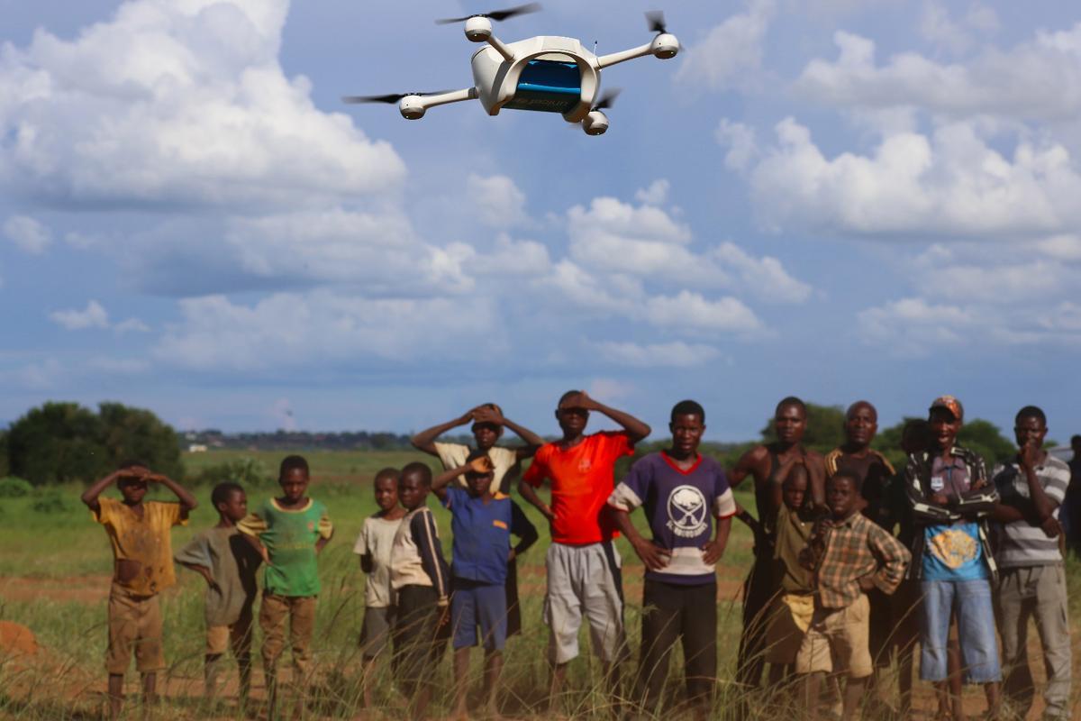 Children in Malawi watch a community drone demonstration in Lilongwe