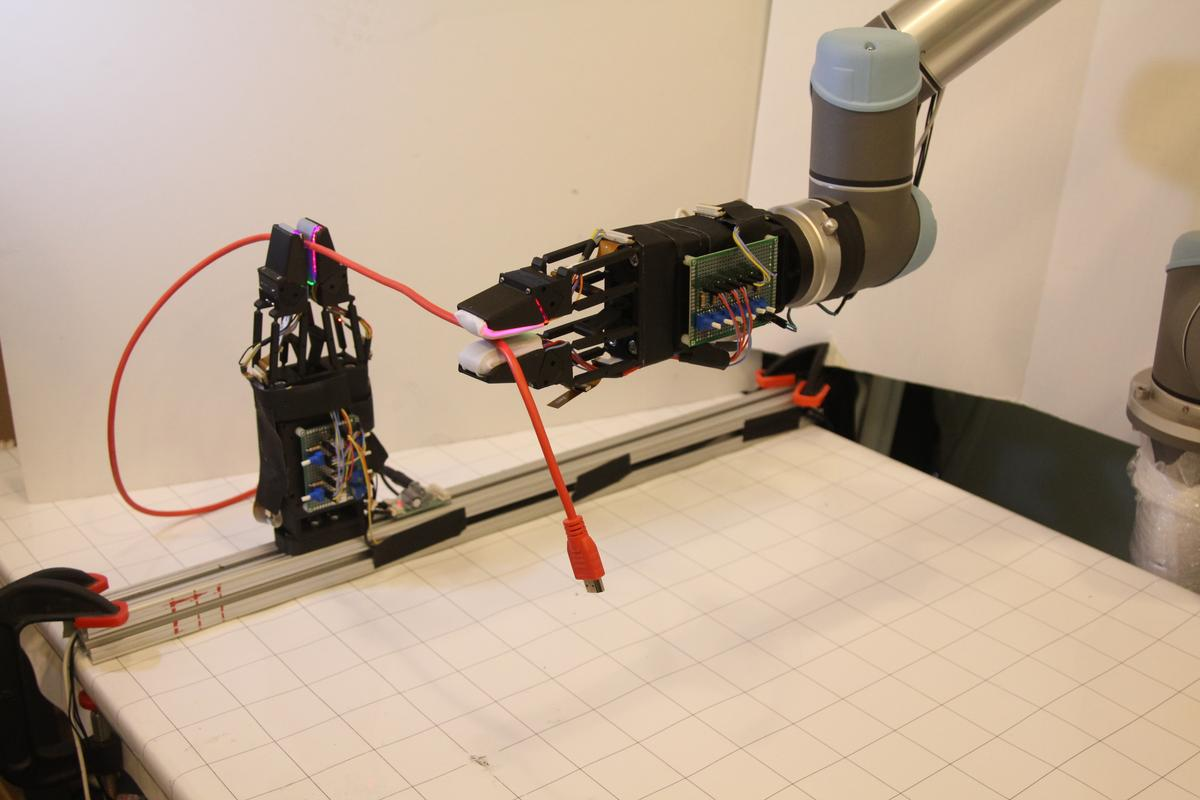 A GelSight-enabled gripper is able to move along the length of a USB cable, without dropping it