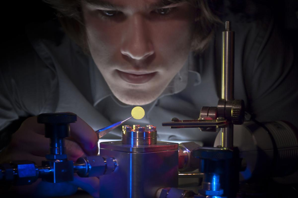 Eric Glowacki, one of the membrane's inventors, is pictured holding the membrane that changes permeability with different colors of light (Image: University of Rochester)
