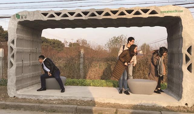 Passengers admire WinSun's 3D-printed bus shelter