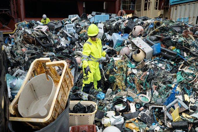 Член на екипа на проекта за почистване на океана пресява пластмасовите отпадъци
