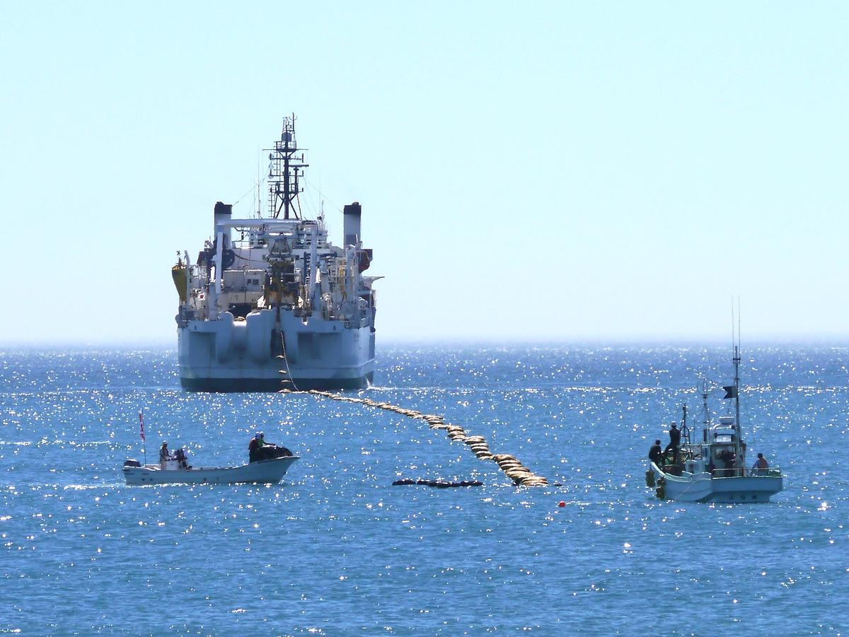 The brown bag-like objects are floats that hold the cable up so it doesn't drag on the ocean floor – they are removed after the cable is run