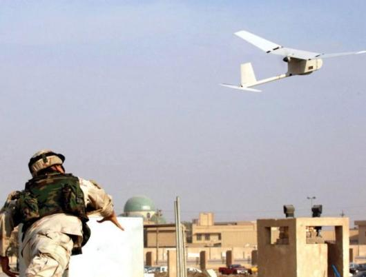 Sgt. Juan Rivera, from 1st Battalion, 9th Field Artillery Regiment, 3rd Infantry Division, launches the RAVEN unmanned aerial vehicle into the skies over downtown Baghdad, to take surveillance photos during December, 2005