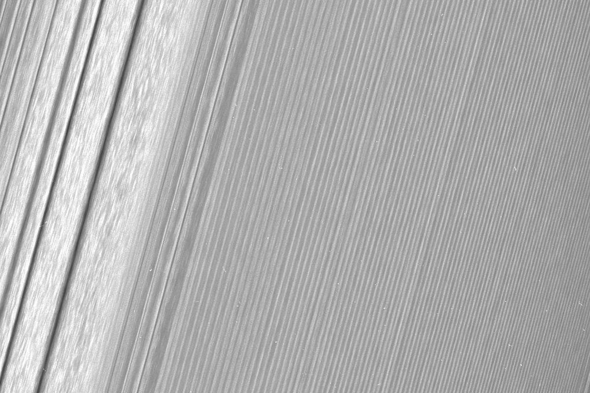 Cassini image of Saturn's A ring featuring a density wave (to the left) and themore subtle wakes created by a ring moon (to the right)