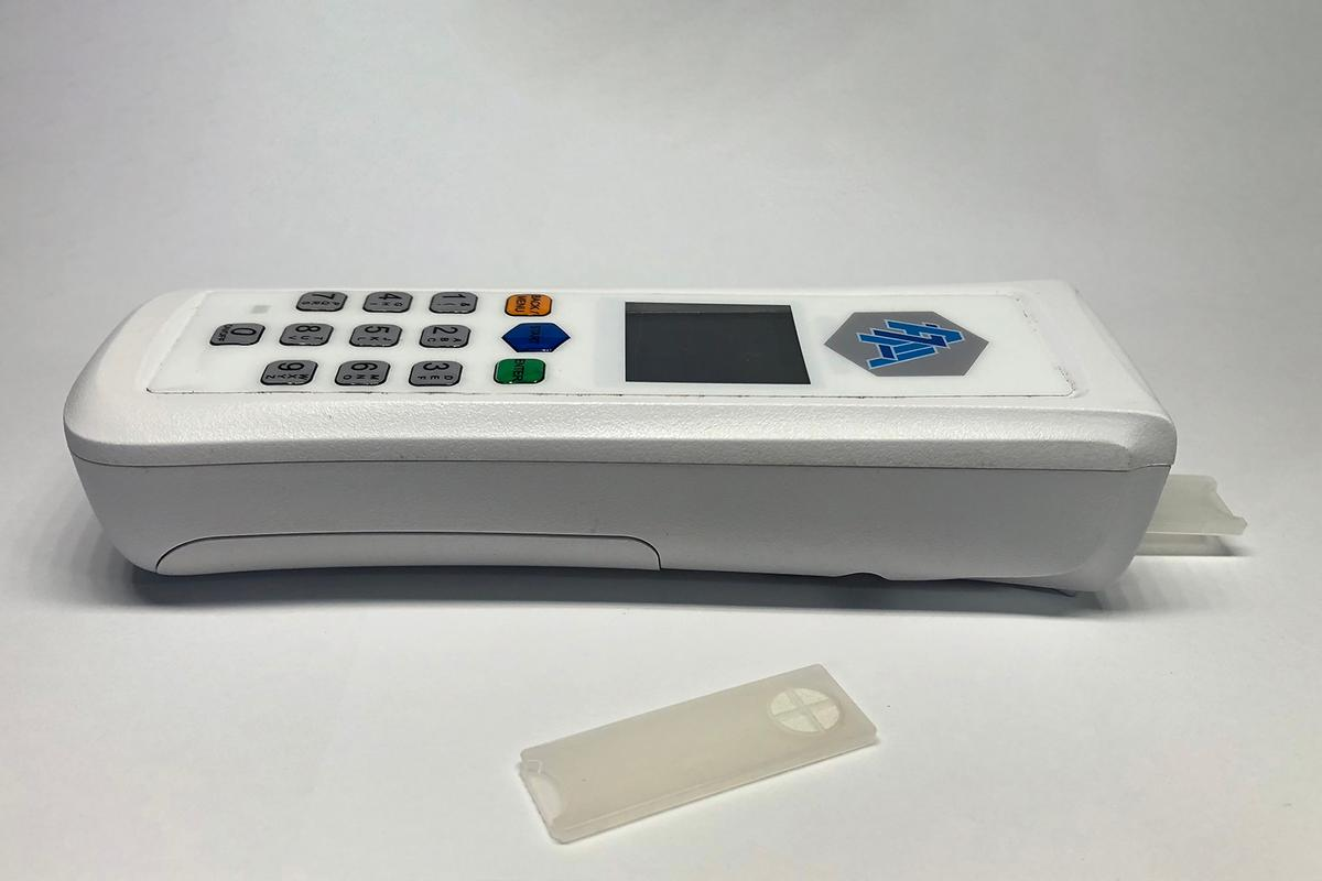 The device (pictured here with one of its test strips) could be used either by staff in clinics, or by patients in their own homes
