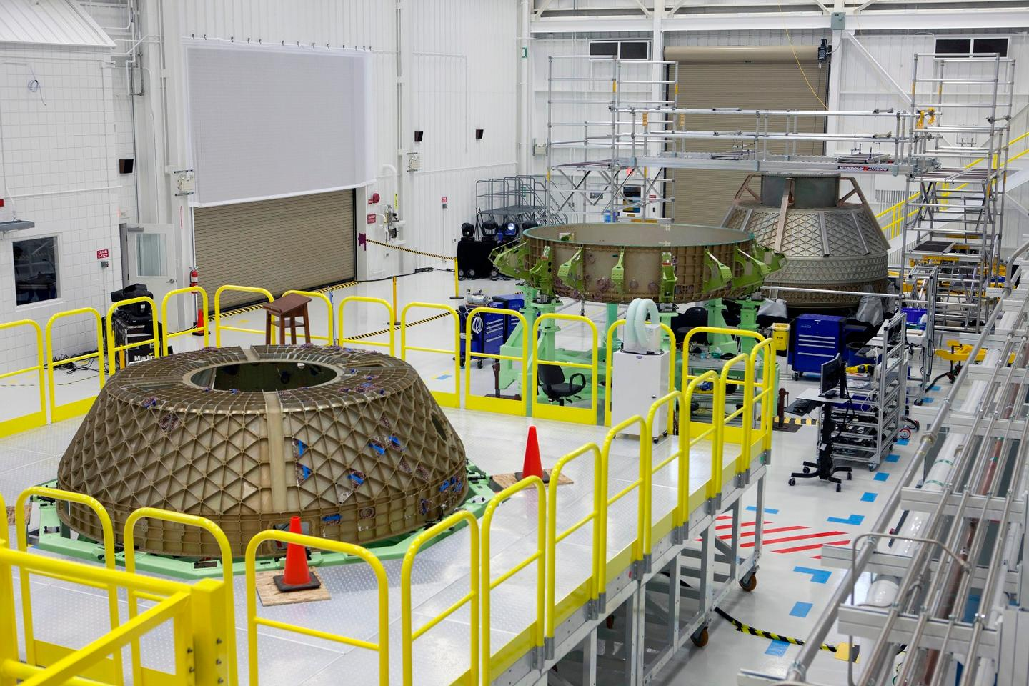 Parts of the Boeing CST-100 Structural Test Article rest on test stands inside the Commercial Crew and Cargo Processing Facility, or C3PF, at NASA's Kennedy Space Center in Florida