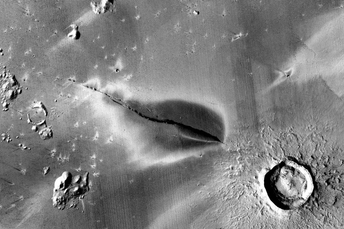 The dark area appears to be a relatively recent volcanic deposit, and the large crater nearby may be connected