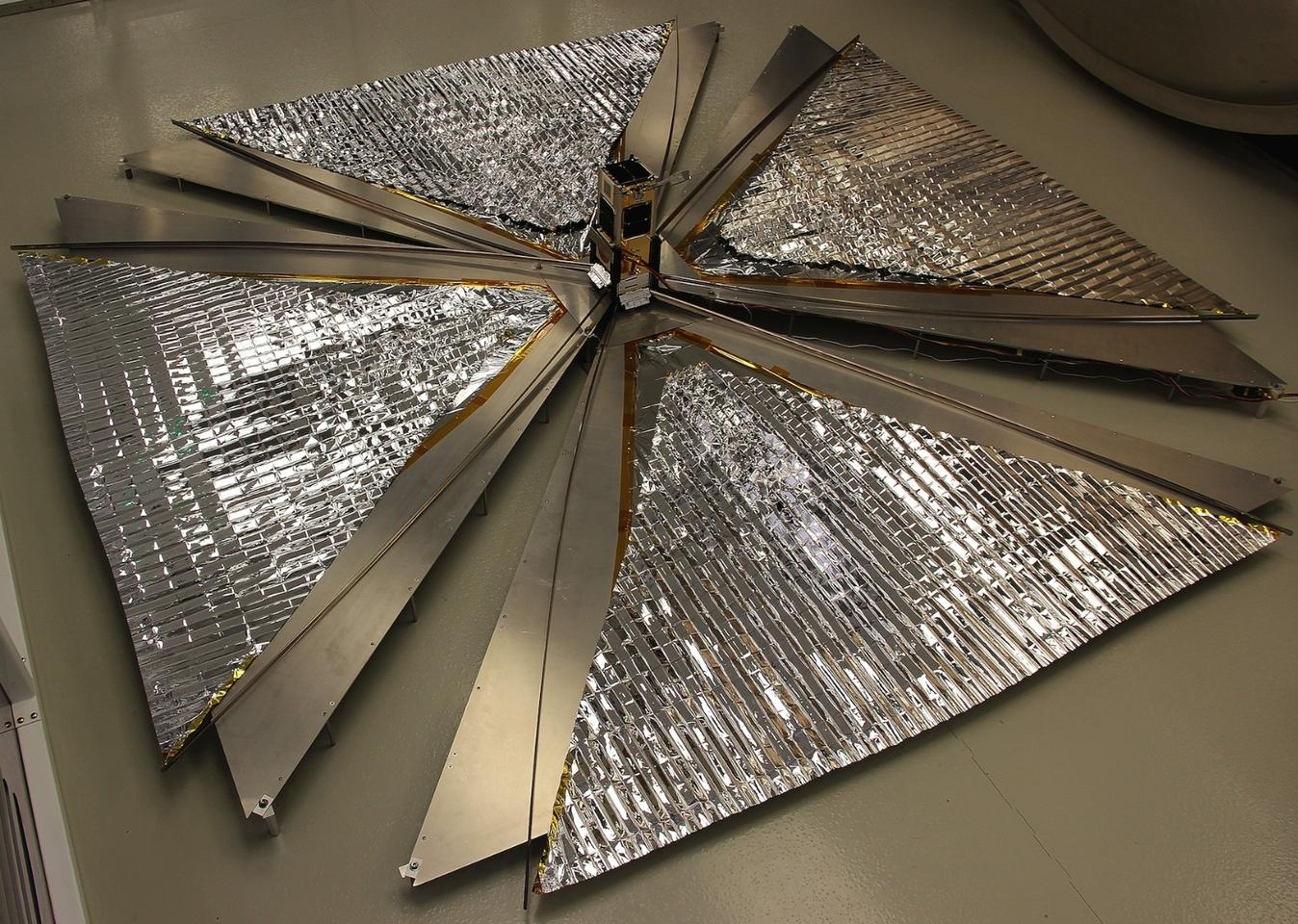 The CanX-7 satellite with its 1 square-meter (10.78 sq ft)drag sails unfurled, in a test before launch