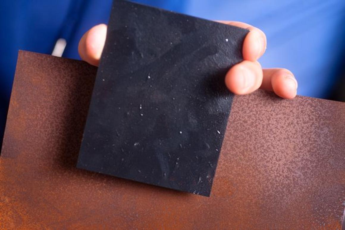 A piece of steel treated with the graphene varnish, in front of an untreated sample