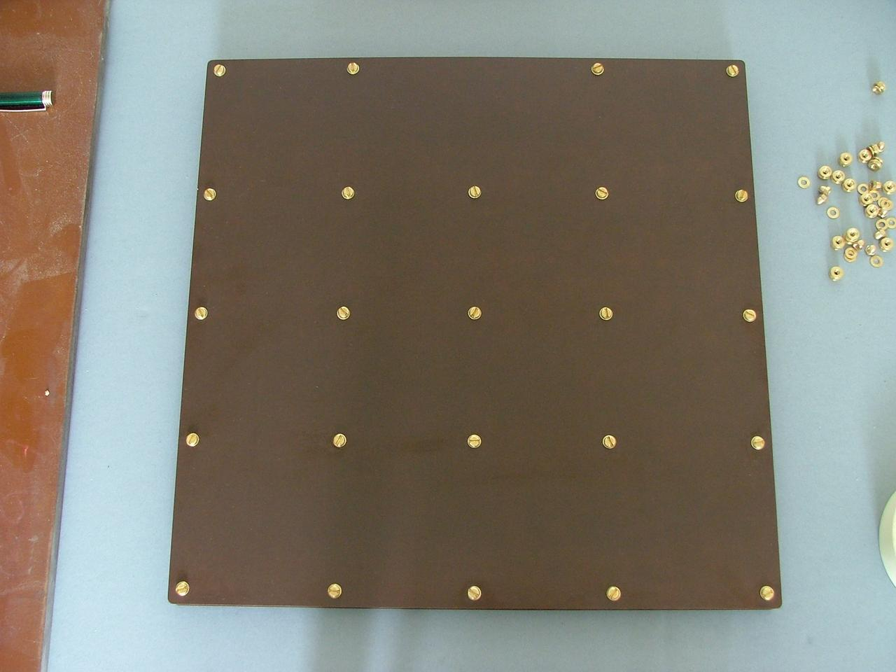 The bottom of the NOS Tufnol and phenolic resin laminate case, showing the placement of brass bolts