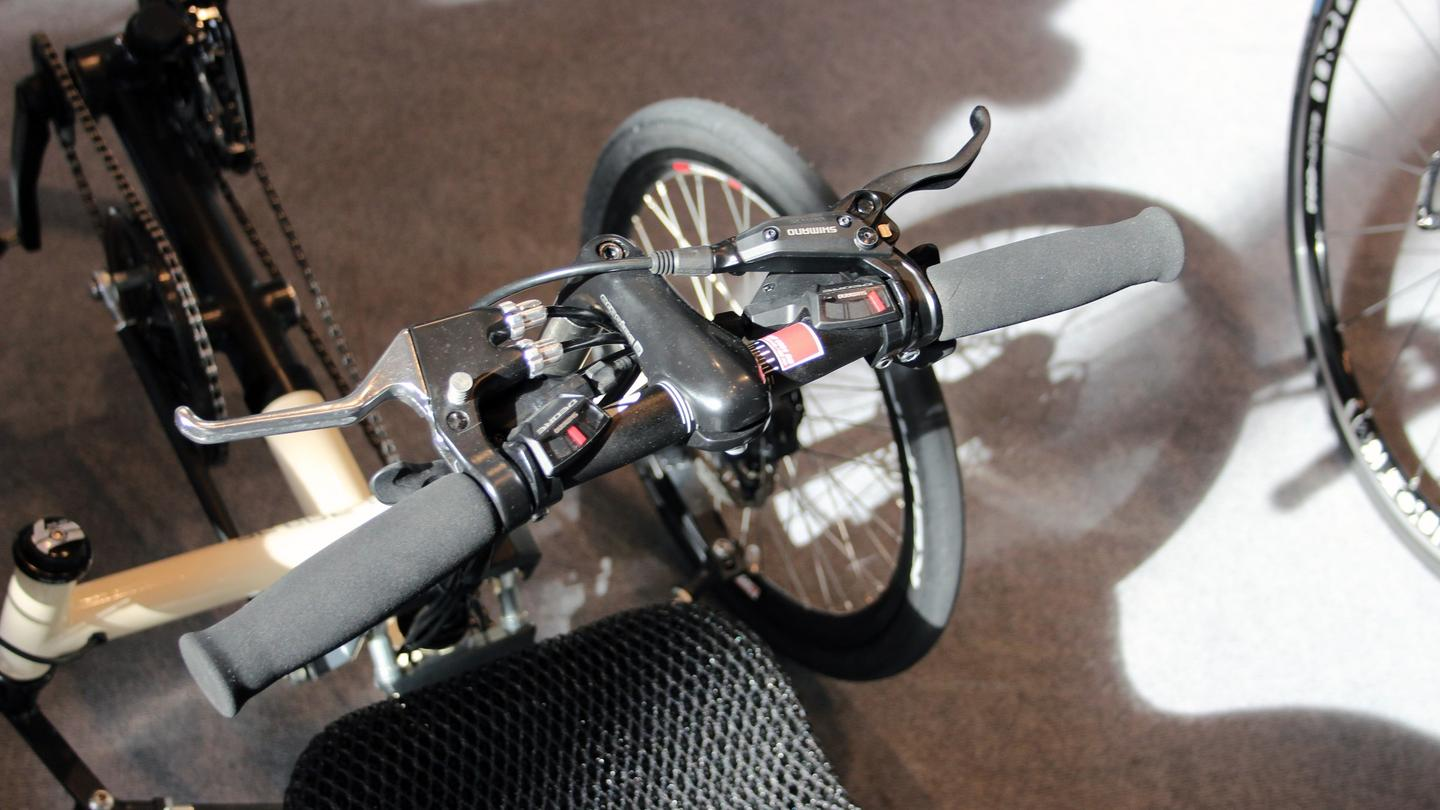 "Instead of the circular arm-cranking motion used on the Varibike, the Ruder Trike has its user ""rowing"" the handlebar column in and out"