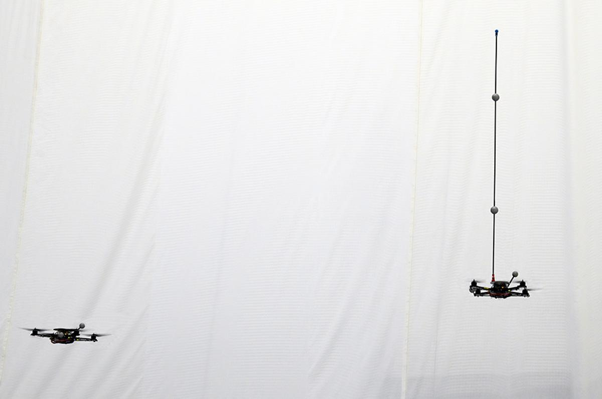 A quadrocopter robot balances a pole while a second robot waits to catch it