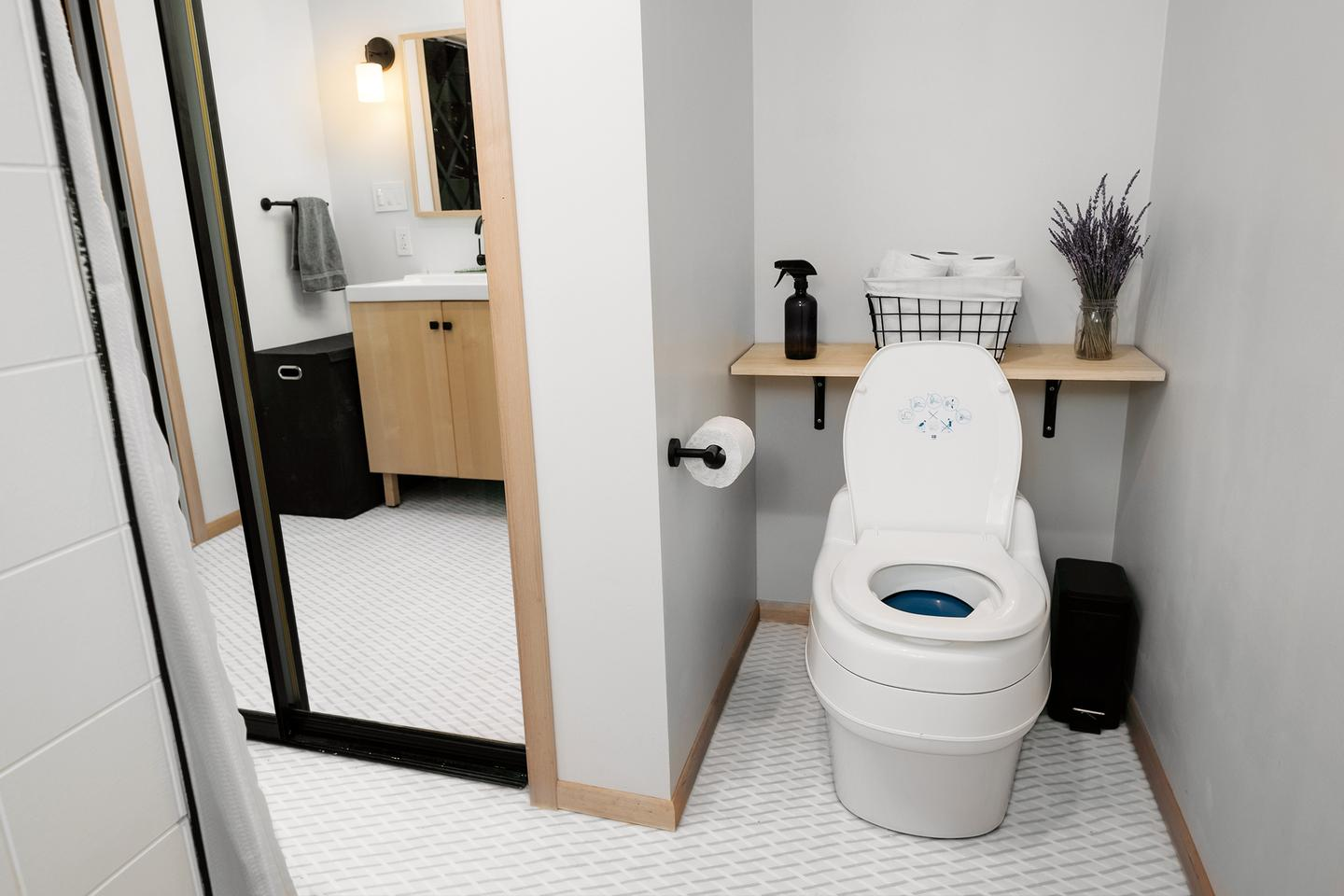 The bathroom features a composting toilet