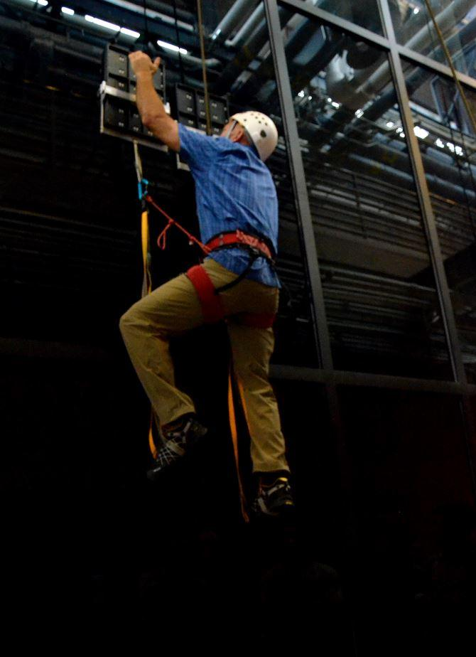 A climber uses the Z-Man paddles to climb up a glass surface