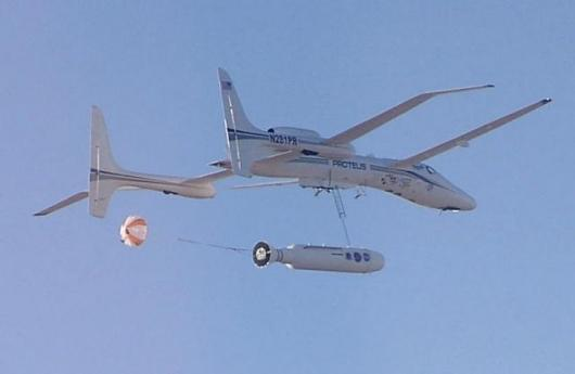 The CXV capsule and its QuickReach II booster are shown one half second after release from the carrier aircrafts. The Trapeze-Lanyard Air Drop mechanism attached to the capsule's nose is fully extended
