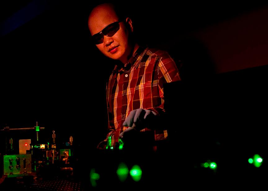 Cuong Dang manipulates a green beam that pumps Brown University's new nanocrystals with energy