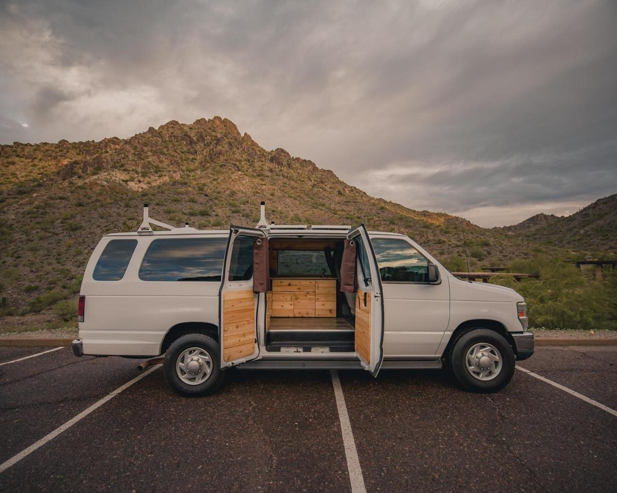 A big, old extended Ford E-350 Boho camper van known as Rev-Van