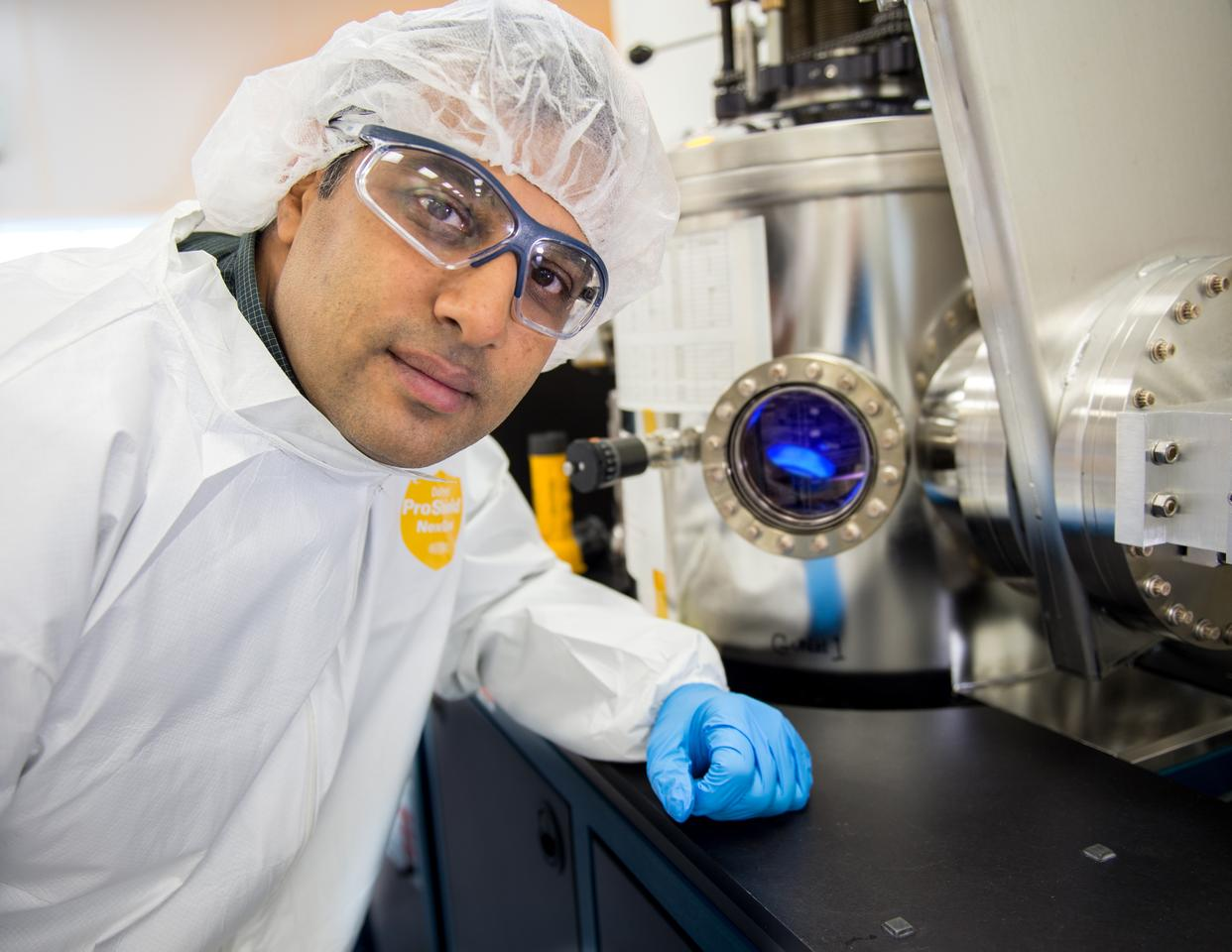 Vivek Dwivedi, in front of a sputtering reactor used to deposit vanadium-oxide onto sample substrates