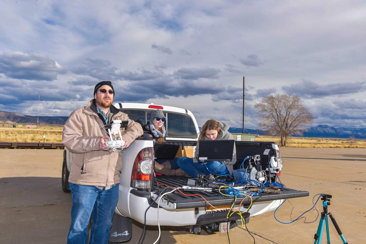Camron Kouhestani, left, flies an unmanned aircraft system while Jaclynn Stubbs, center, and Bryana Woo monitor a camera stream at Sandia National Laboratories