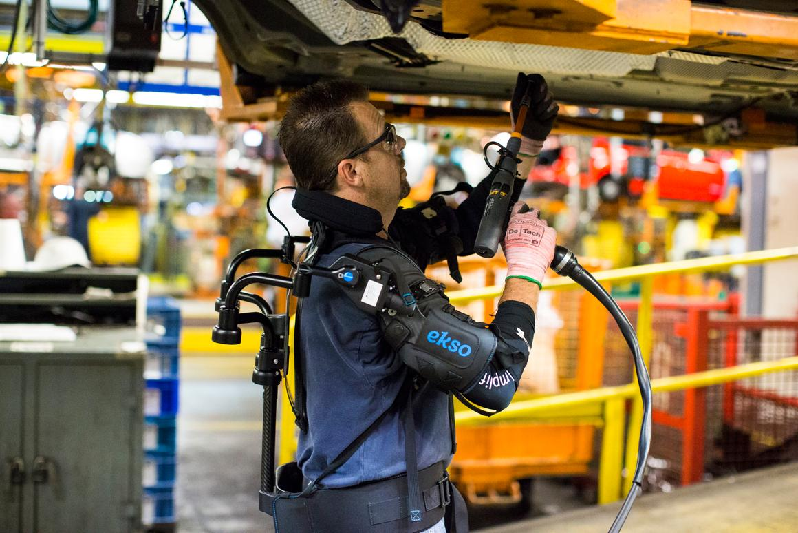 A ford employee utilizes the EksoVest