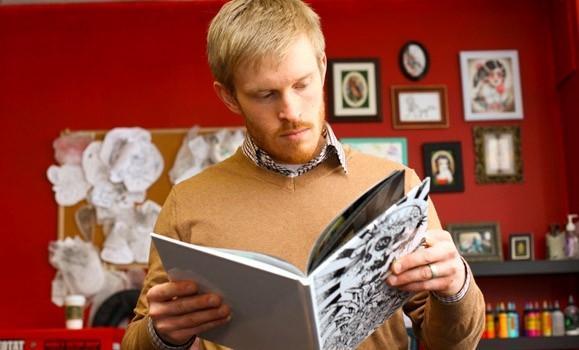 PhD student Alec Falkenham, inventor of the cream, studies a book of tattoos (Photo: Bruce Bottomley photos)