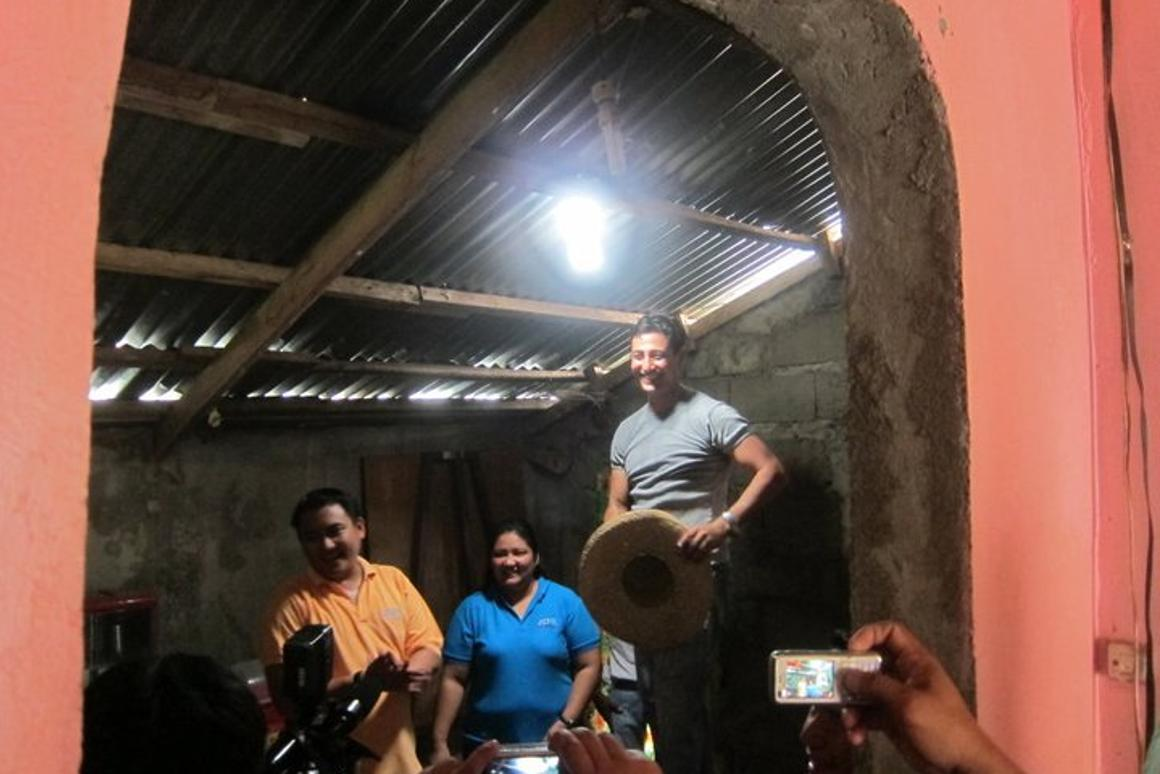 Illac Diaz (right) in a home equipped with one of his Solar Bottle Bulbs(Photo: Isang Litrong Liwanag)