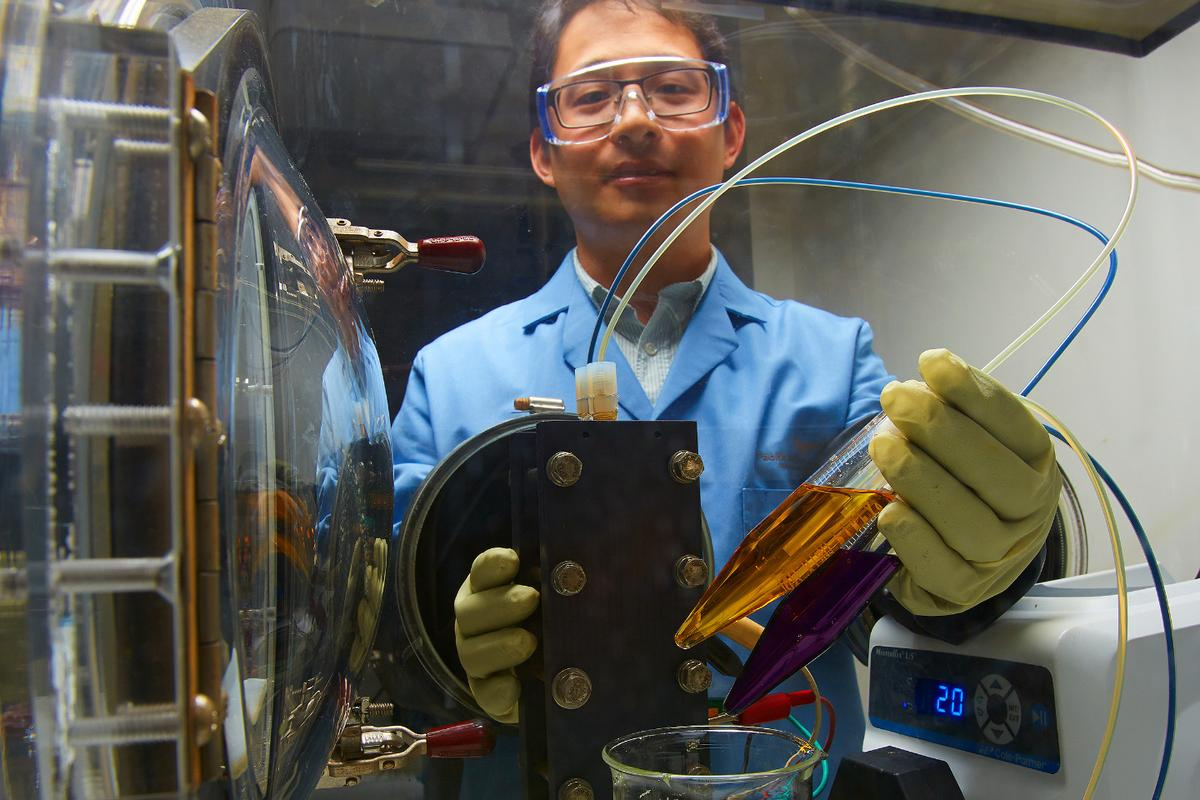 A new flow battery technology is expected to cost substantially less and be better for the environment thanks to its organic water-based electrolytes, as seen here in a small demonstration by PNNL researcher Xiaoliang Wei