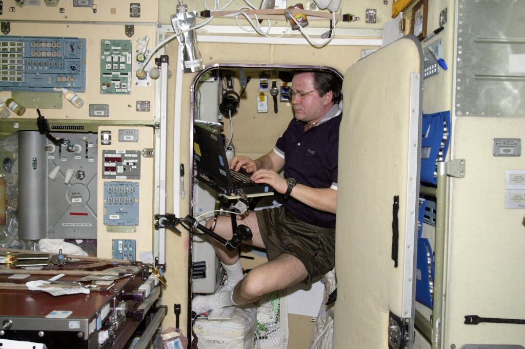 Cosmonaut Nikolai M. Budarin, working in his sleep station in the Zvezda Service Module aboard the ISS (Photo: NASA)