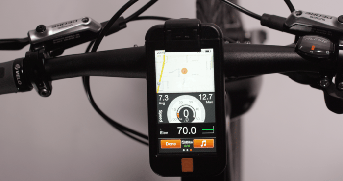 An iOS companion app displays information such as speed, cadence, elevation and a map for navigation