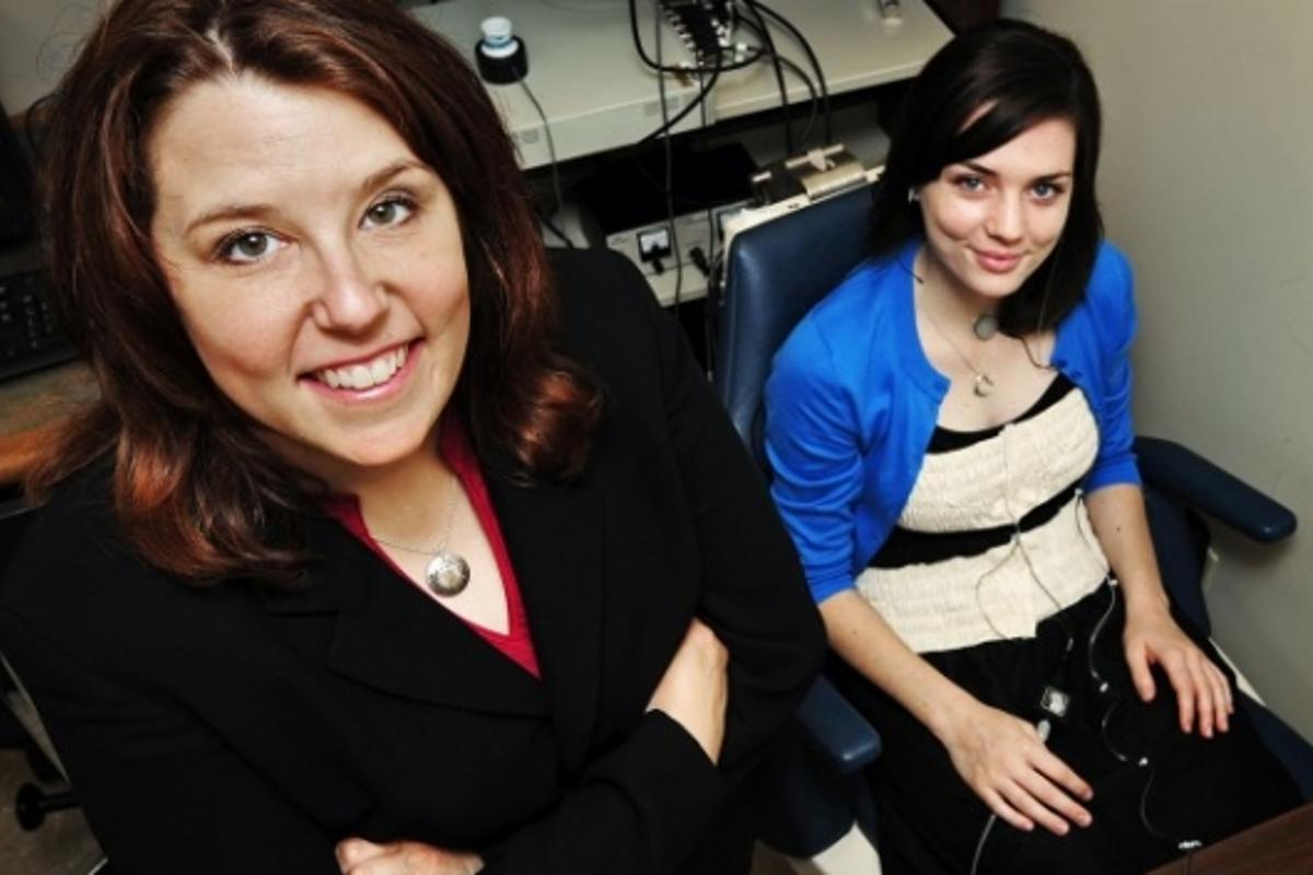Jessica Huber,left, and graduate student Meghan Moran demonstrate the technology developed by Huber that helps Parkinson's patients overcome the tendency to speak too quietly.