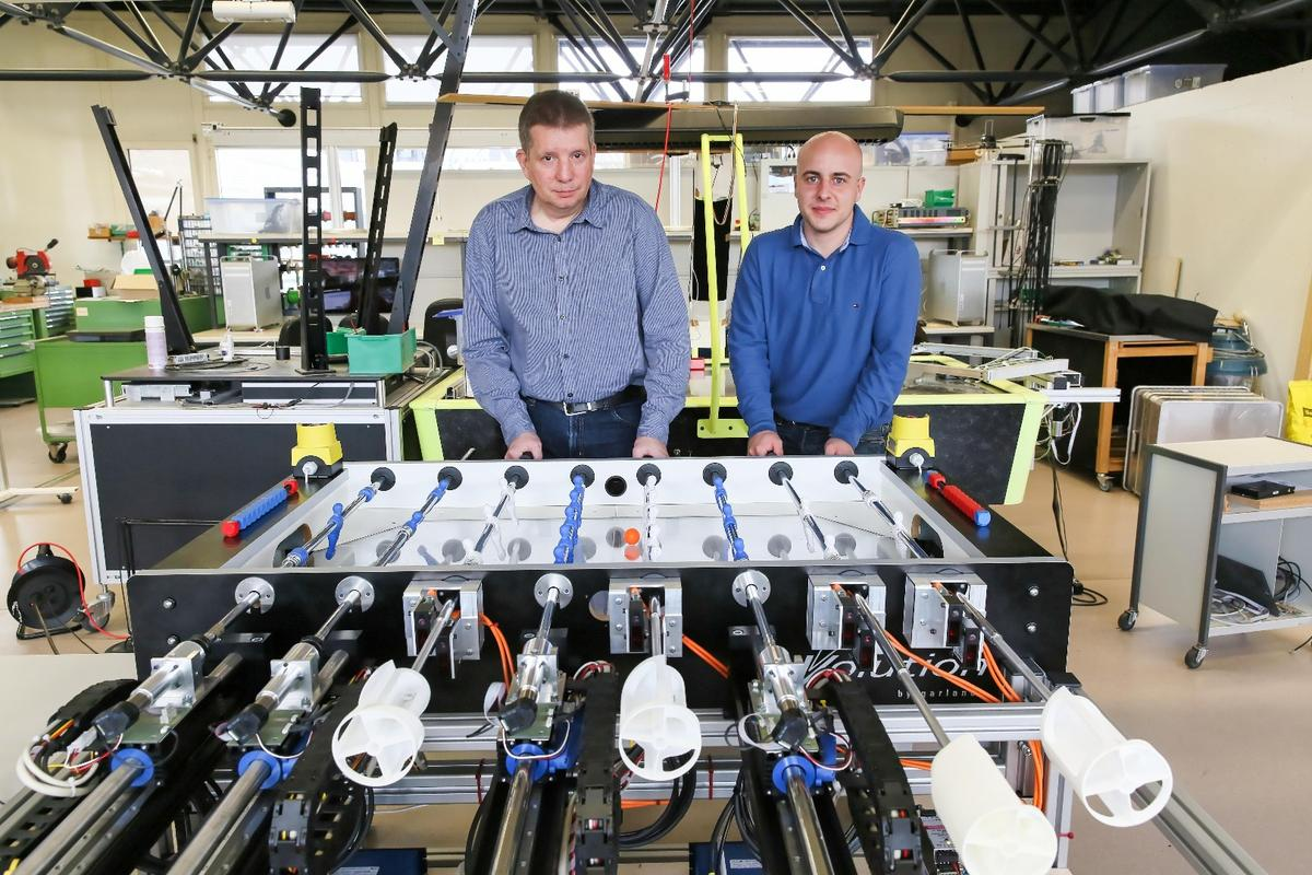 EPFL researchers prepare to do battle with the robot foosball system