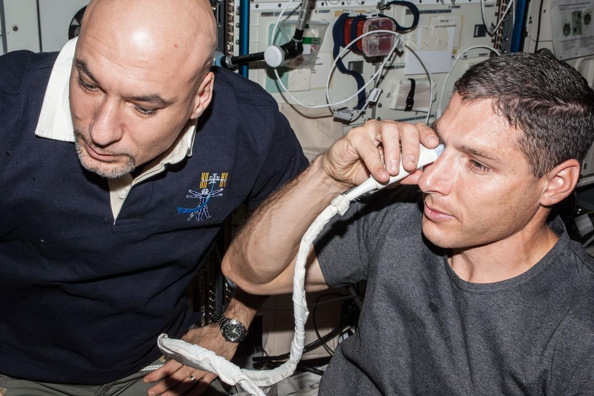 Astronaut Micheal Hopkins performs an ultrasound scan on his eye (Image: NASA)