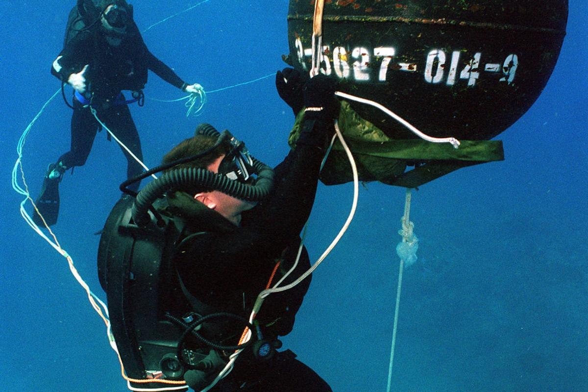 US Navy divers with a practice mine