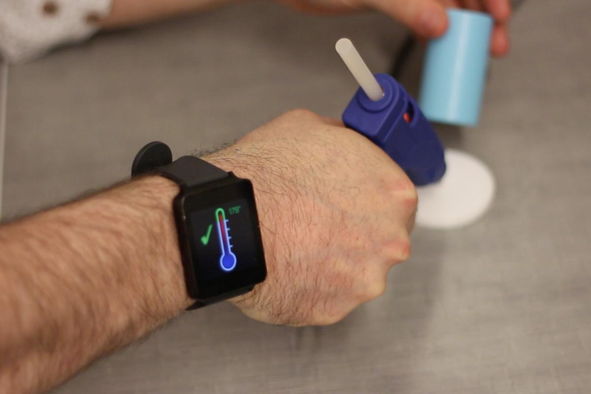 A ViBand-equipped smartwatch communicates with a vibro-tagged glue gun, using bio-acoustic signals