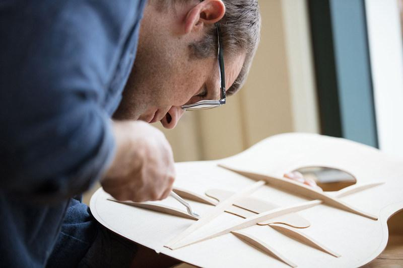 Taylor's master designer Andy Powers works on fan braces extending out from the center V-brace of an acoustic guitar's soundboard