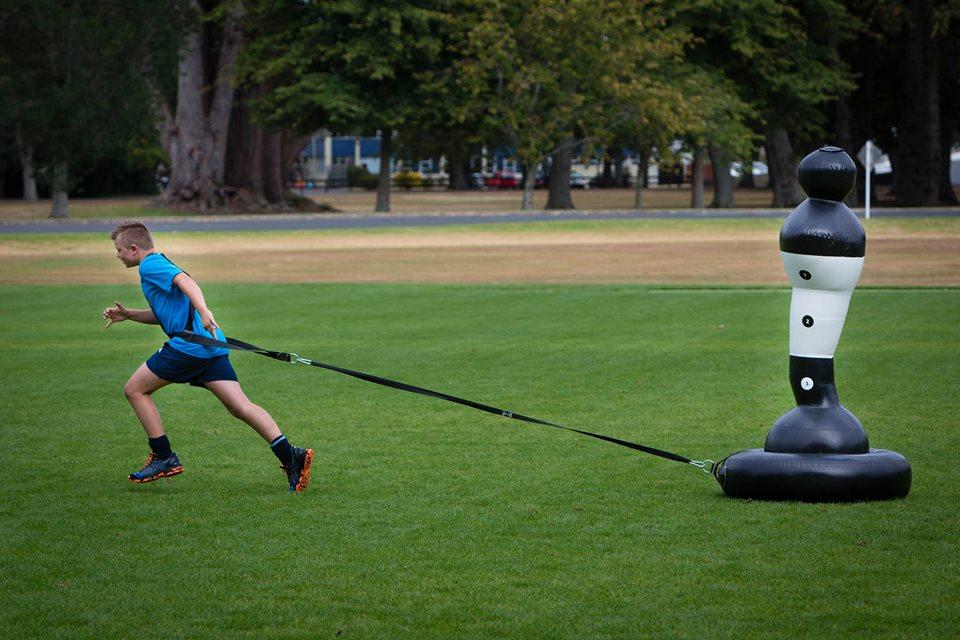 The Shadowman Junior sits on top of a separate tire-like base that's dragged across the turf by a coach or another player using an attached strap/harness, as players are trying to tackle it