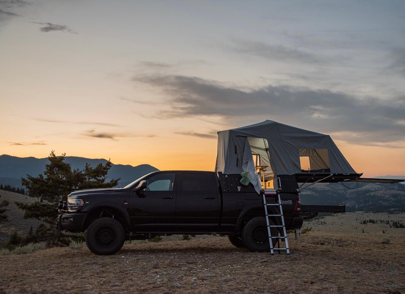 The Skinny Guy pickup topper is designed to sleep two and seat up to four inside its tent