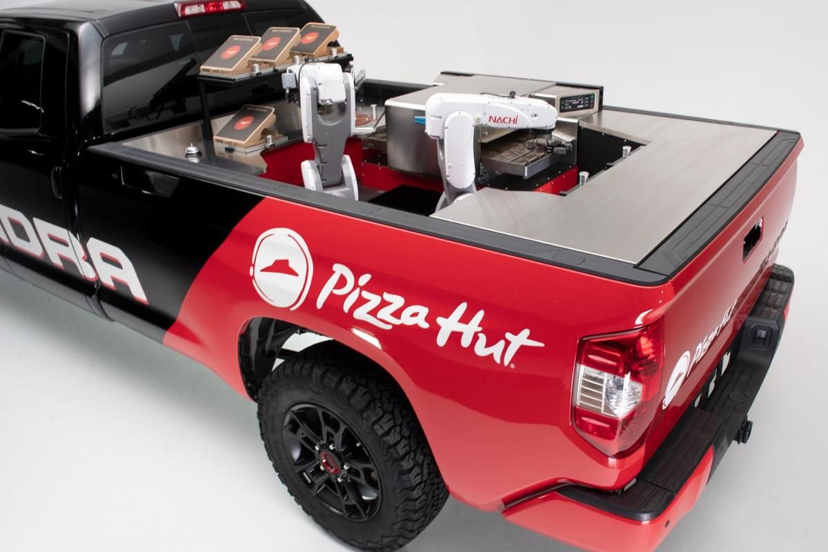 The Tundra Pie Pro's mobile pizza factory consists of two robotic arms, a refrigerator, and a high-intensity conveyor oven