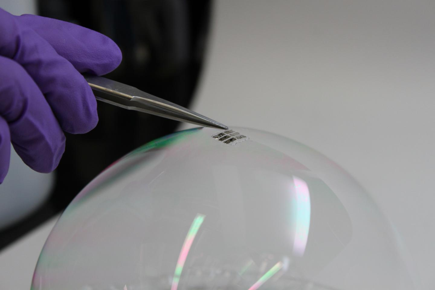 Researchers at MIT have created prototype solar cells so light and so thin, that they can be balanced on the surface of a soap bubble without breaking it