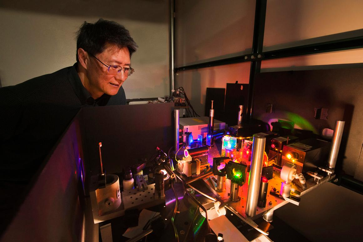 Researcher Jeff Tsao examines the set-up used to test diode lasers as an alternative to LED lighting (Photo: Randy Montoya)