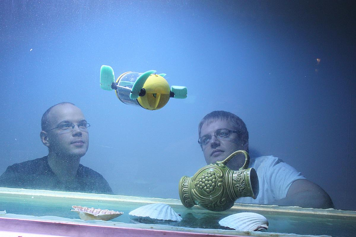 Tallinn University of Technology researchers Asko Ristolainen and Taavi Salumäe watch the U-CAT robot in an aquarium