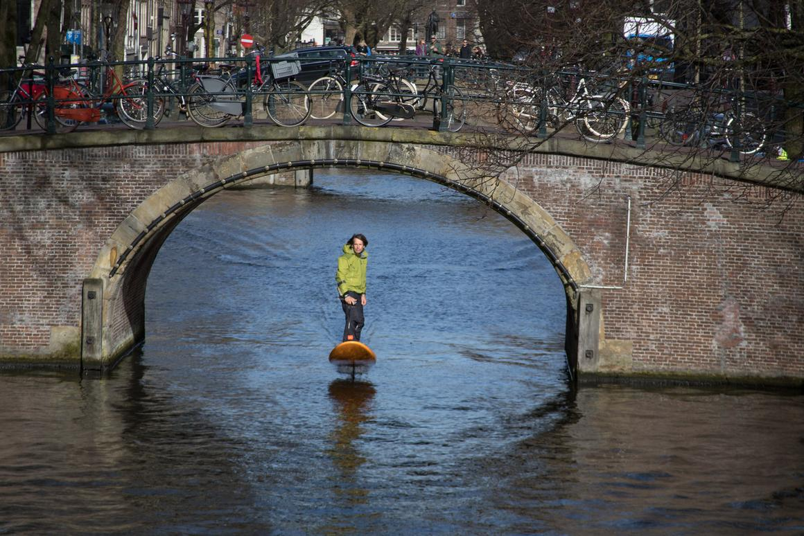 Inventor Don Montague rides his Jetfoiler board along Amsterdam's canals