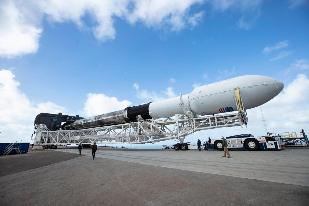A scorchedFalcon 9 is rolled out to the launchpad