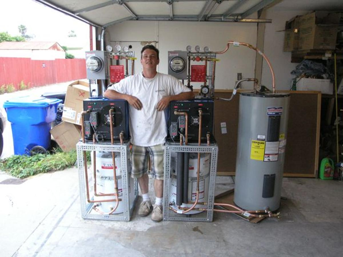 A prototype water heater system that uses cold water to make hot water pictured with Slater's assistant, David Dawson