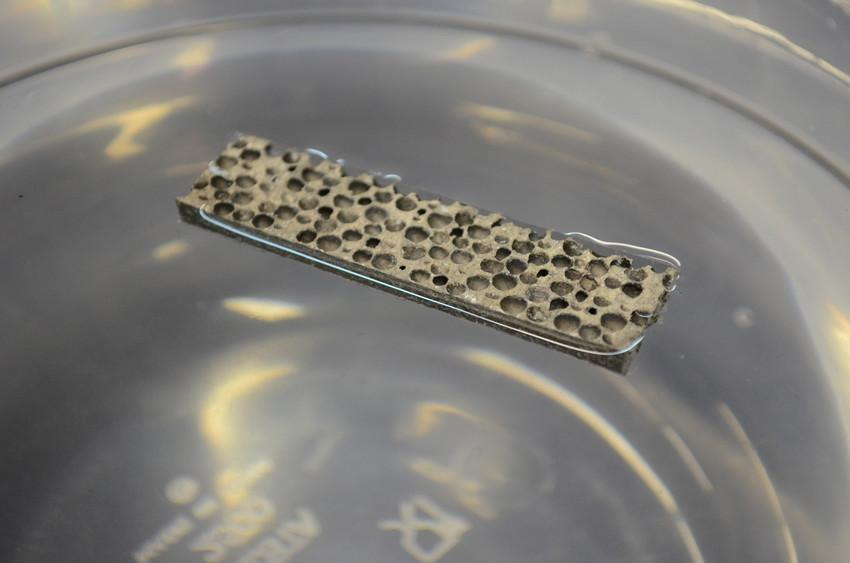 The new lightweight metal matrix foam floating in a beaker of water